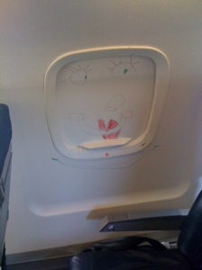 Clown face drawn on inside of window shade in row 8